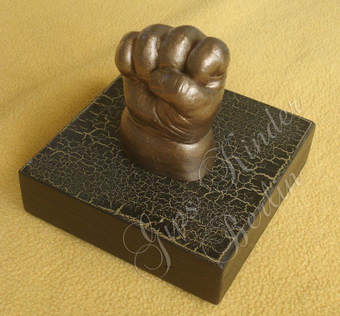 Bronzebabyhand auf Podest schwarzgold