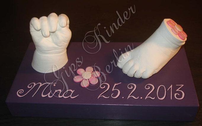 Babyfuß & Babyhand auf einfachen Podest mit Perlmutblumen