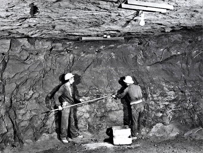 Bergmänner verfüllen Bohrlöcher mit Sprengstoff.