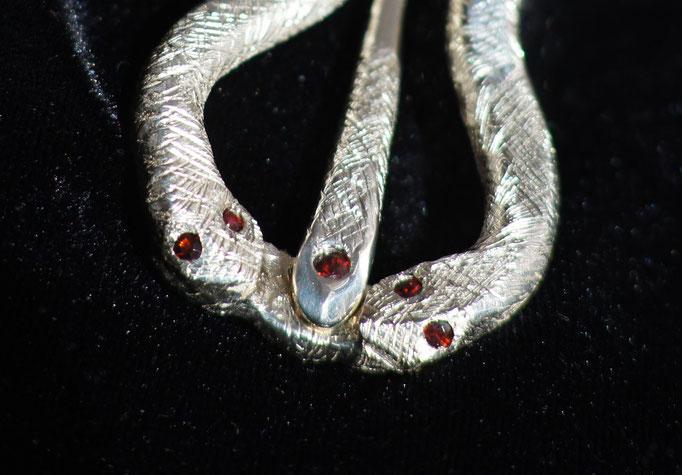 Schmuckstück: Verspielte Gürtschnalle aus Silber und Granat, Züngelnde Schlangen umwinden einen Ast, Nahaufnahme Schlangenköpfe