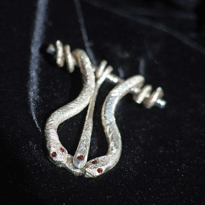 Schmuckstück: Verspielte Gürtschnalle aus Silber und Granat, Züngelnde Schlangen umwinden einen Ast