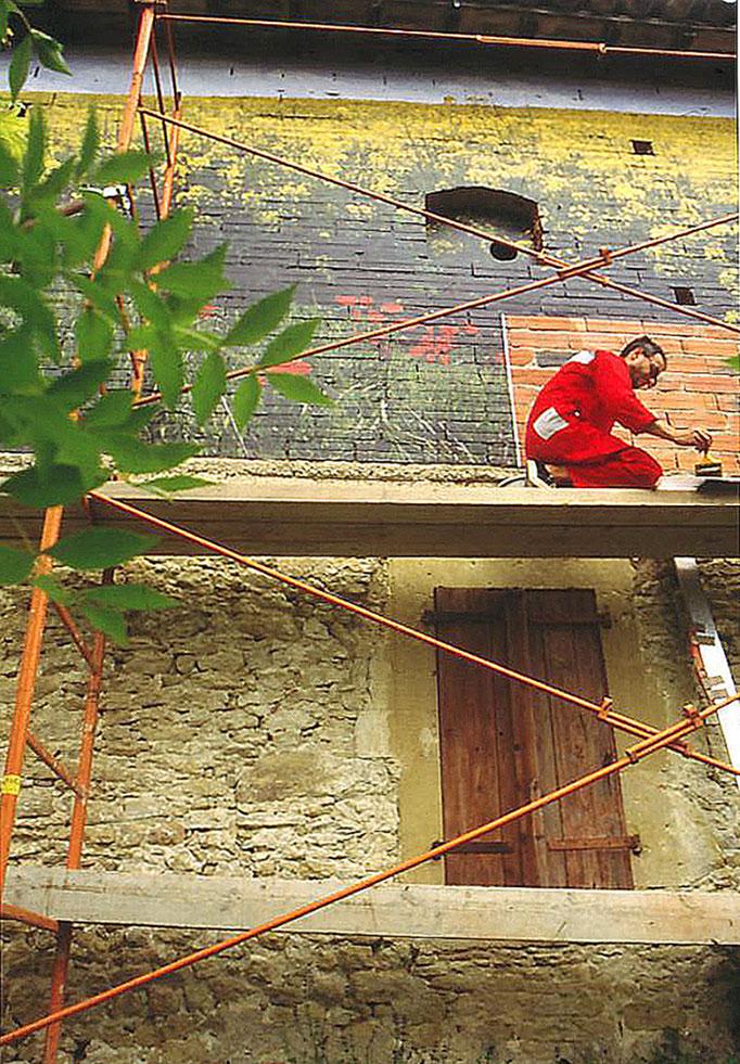 Mise en oeuvre de la fresque photographique par collage de plusieurs centaines d'images laser couleur (format A3) minutuieusement numérotées puis marouflées sur la façade en brique.