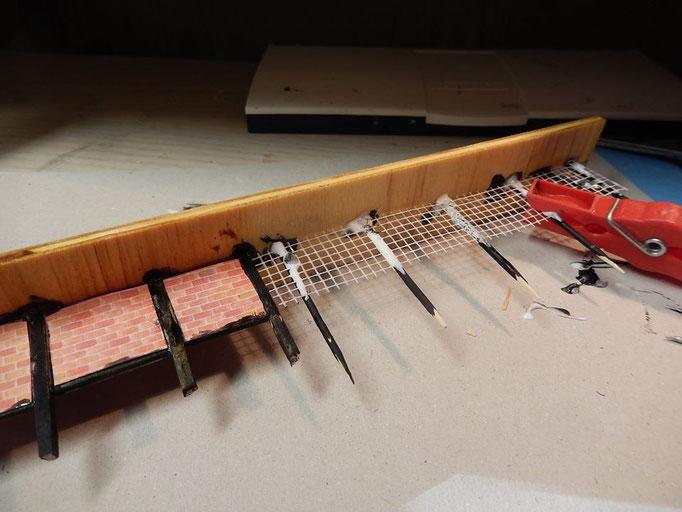 Der Zaun wird passend geschnitten und aufgeklebt . Wäscheklammern zum fixieren.