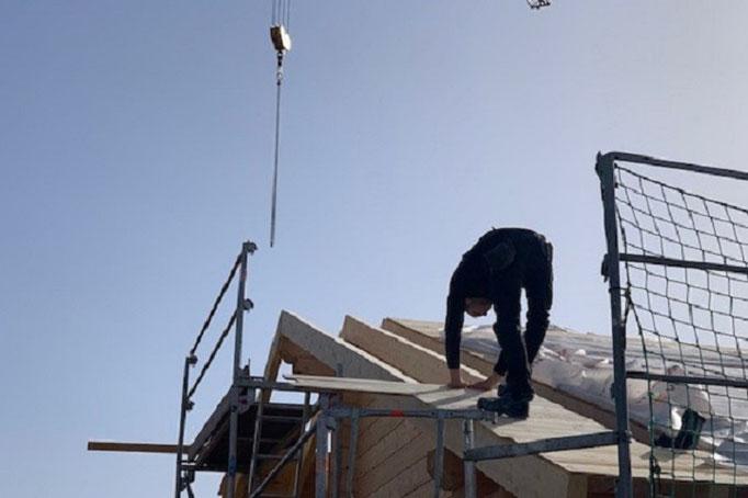 Wohnblockhaus - Blockhausbau - Schalung der Traufe - Arbeiten auf dem Dach in Bayern