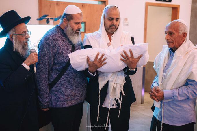 האב מחזיק התינוק לפני החיתוך