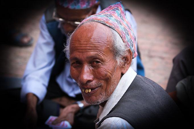 ein Kartenspieler in einem Innenhof in Patan