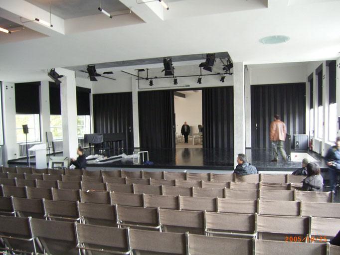 講堂から舞台、背後が半開きで食堂が見える