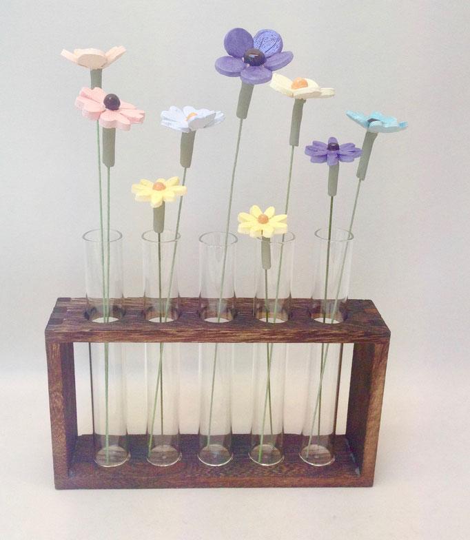 Kleine bloempjes in glazen buisjes in houten rekje