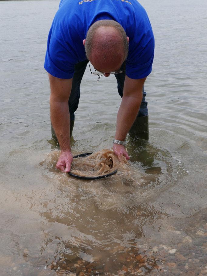 Das Kies-Sand-Schlamm und Magnetit.Gemisch wird gewaschen, bis nur noch der schwarze Magnetit bleibt