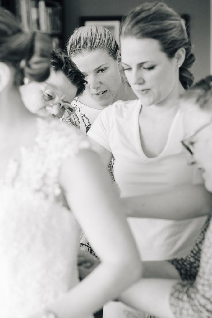 Hochzeitsreportage - Getting Ready der Braut - Knöpfen des Brautkleidkorsetts