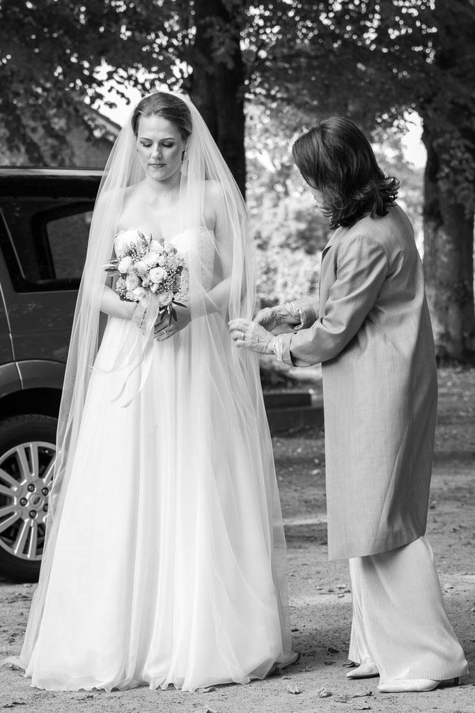 Hochzeitsreportage - der letzte Feinschliff am Brautkleid vor dem Einzug in die Kirche