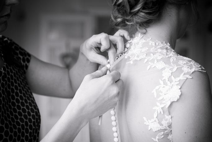 Hochzeitsreportage - Vorbereitung der Braut - Brautkleid wird zugeknöpft