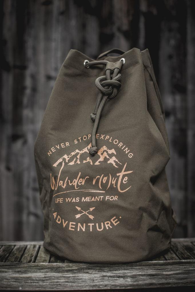 olive Outdoor Rucksack mit gepolsterten Trägern. Rucksack mit 2 extra fächern im Turnbeutel style. Mit Wanderlust Quotes Motivdruck.
