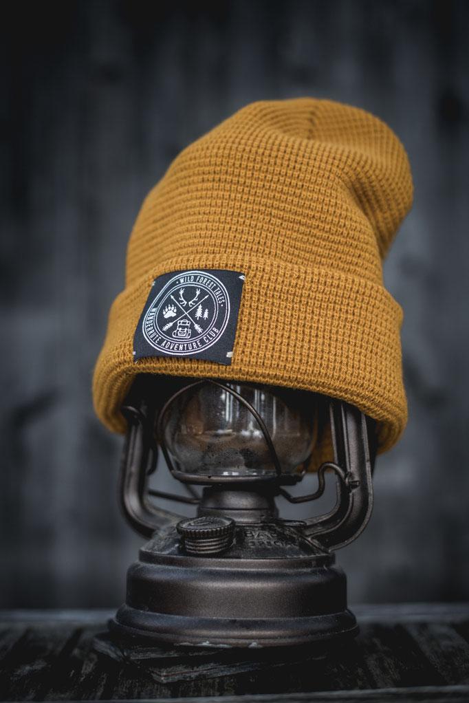 gelbe Strickmütze mit Abenteuer Label Patch auf der Vorderseite. Cooles Waffel Strickmuster mit breitem Umschlag.