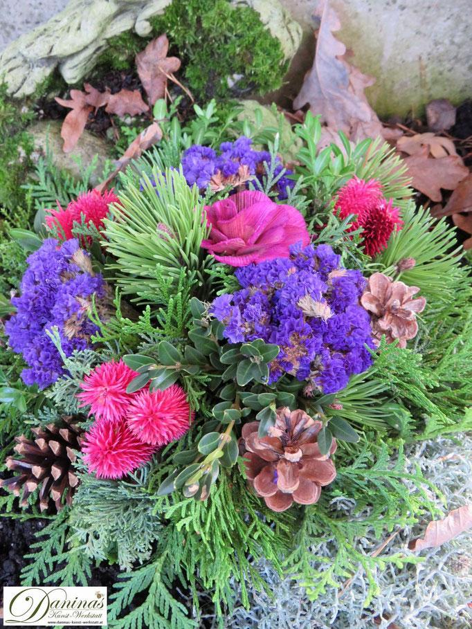 Grabgesteck Allerheiligen: Nadelbaumzweige mit Zapfen sowie rosa und blauen Blumen