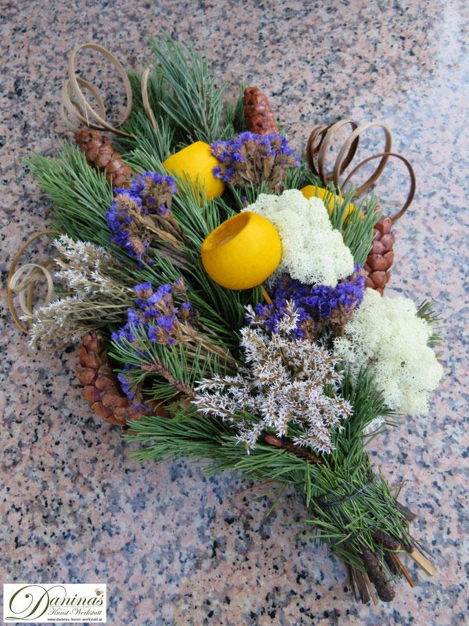 Allerheiligengesteck aus Kiefernzweige, Zapfen, blauen und weißen Blumen und gelben Samenschalen