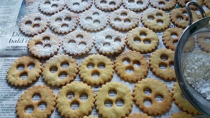 Keks-Oberteile (mit Löchern) mit Staubzucker bestäuben