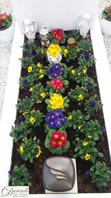 Grabbepflanzung mit bunten Primeln und Stiefmütterchen