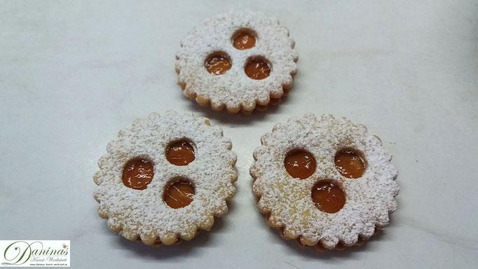 Keks-Oberteile (mit Staubzucker) auf die mit Marmelade betrichenen Unterteile setzen