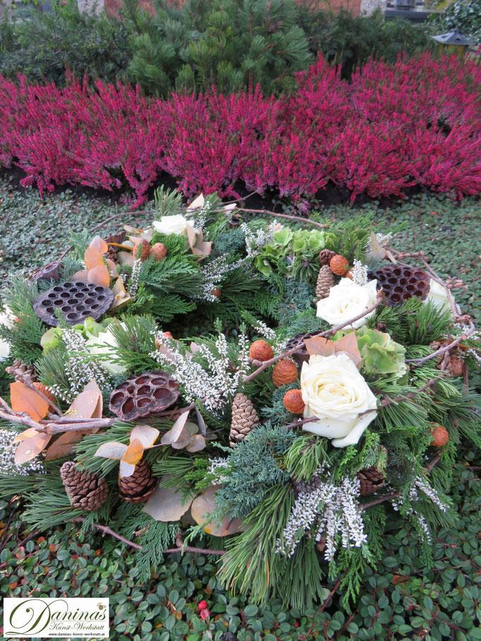Grabgesteck Allerheiligen: Kranz aus Nadelbaumzweigen, Zapfen und weißen Rosen
