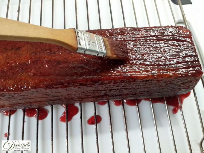 Ribiselmarmelade gleichmäßig auf dem Kuchen verteilen