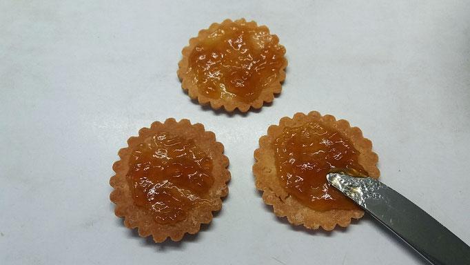 Keks-Unterteile mit Marillen Marmelade bestreichen