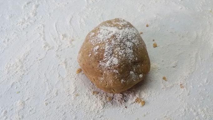 Nuss-Mürbeteig zu einer Kugel formen und mit Mehl bestäuben