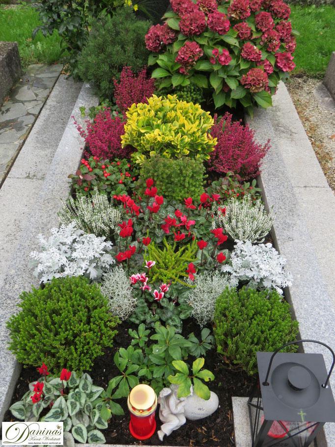 Herbstliche Grabbepflanzung Idee mit bunten Blumen.