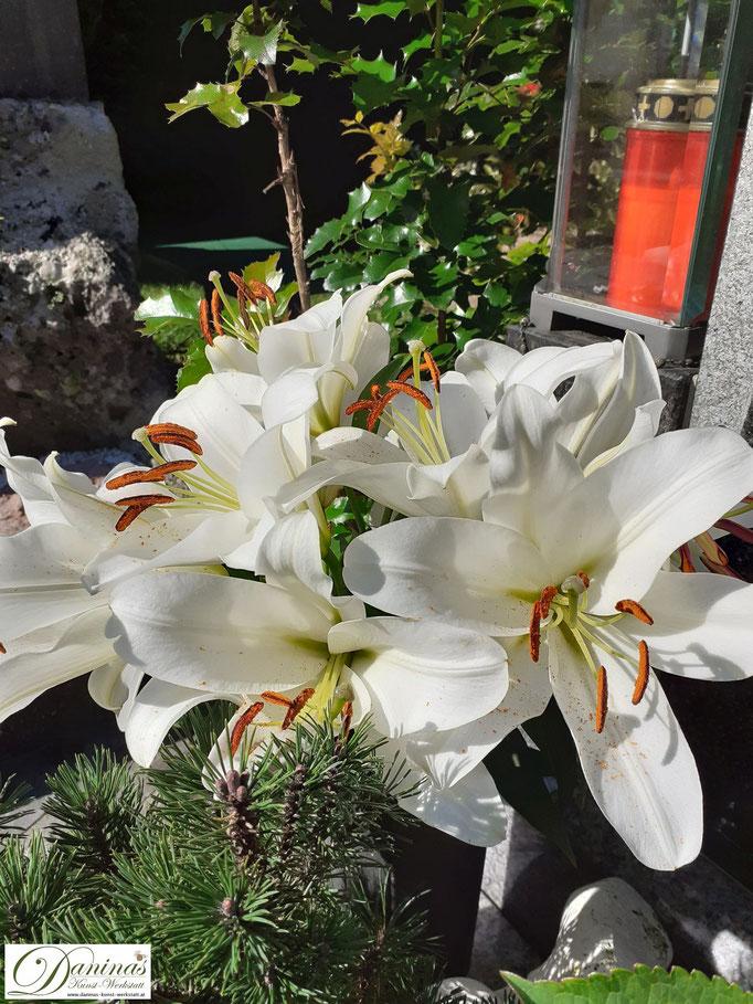 Grabgestaltung Herbst mit weißen Lilien in der Vase