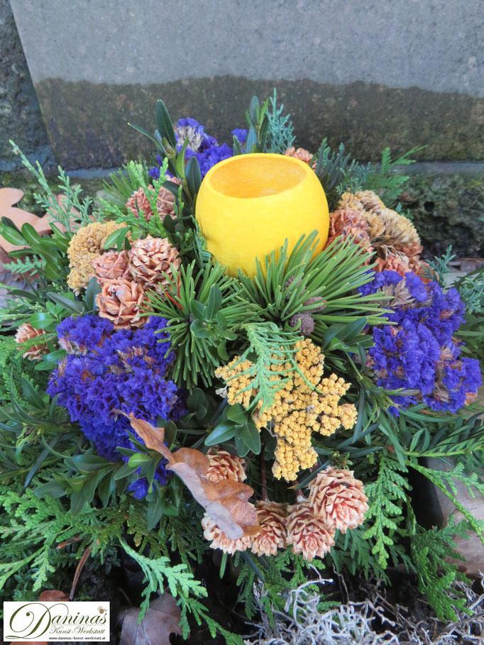 Grabgesteck Allerheiligen: Kiefernzweige, Lärchenzapfen, blauen Blumen und gelber Samenschale