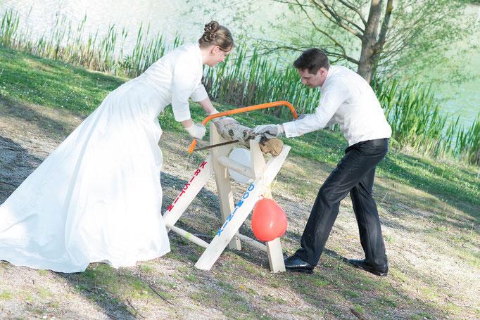 Braut und Bräutigam sägen zusammen den Baumstamm