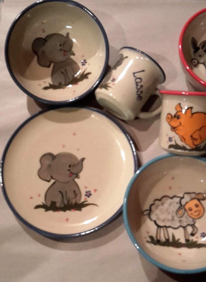 Kindergeschirr (von links nach rechts): Dessertteller, Tasse klein und Müslischale mit Motiv Elefant in blau; Müslischale mit Motiv Schaf in mint; Tasse klein mit Motiv Schwein in koralle
