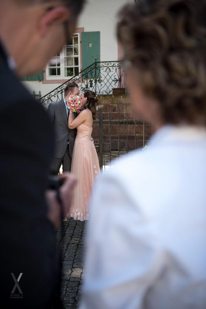 Hochzeit Brautpaar der Kuss hinter dem Brautstrauss