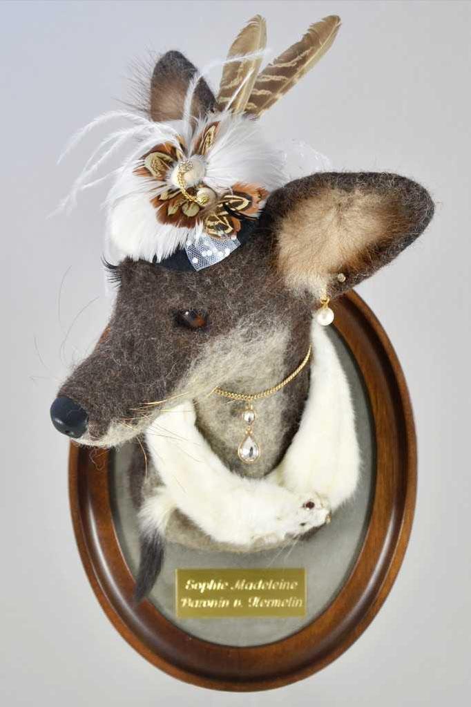 Gefilzter Fuchskopf in einem Holzrahmen als Wanddekoration. Der Trophäenkopf ist als feine Dame von Welt samt Hut und Schmuck gestaltet.