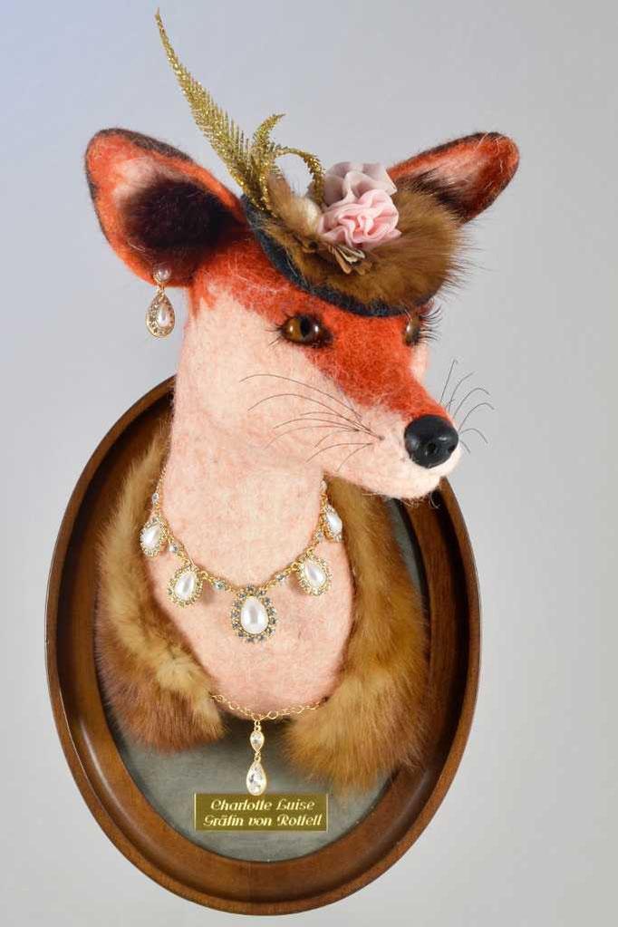 Trophenkopf eines Fuchses aus Rot-weißem Fell. Der Tierkopf ist mit einem Hut, edlem Schmuck und Pelz dekoriert.