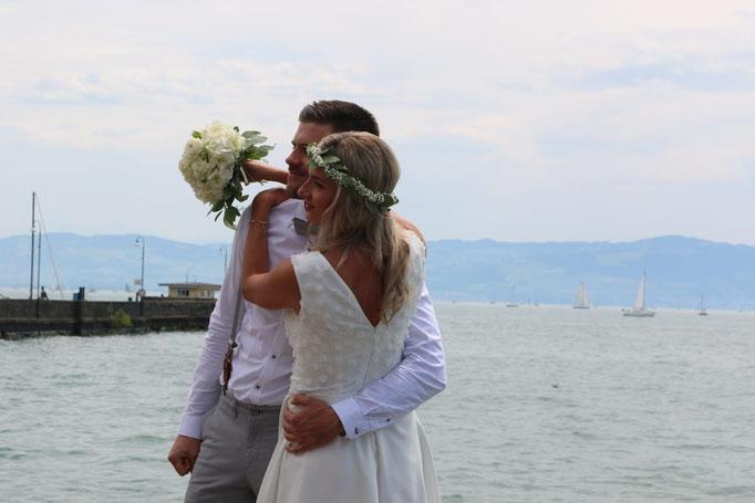 Weißes Brautkleid. Oberteil mit Blütenspitze bezogen und im Vorder- und Rückenteil tief ausgeschnitten.