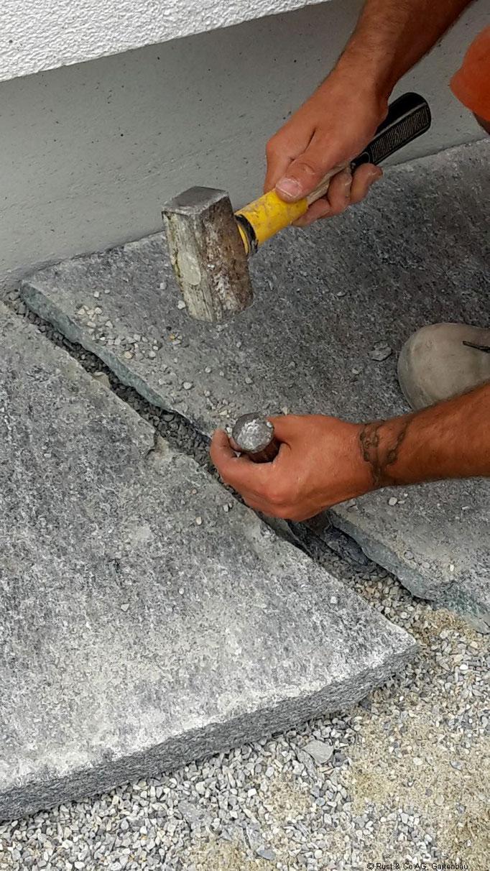 Bearbeiten von Natursteinplatten mit Hammer und Setzer.