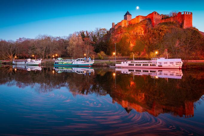 Burg Giebichenstein spiegelt sich auf der Saale im Herbst