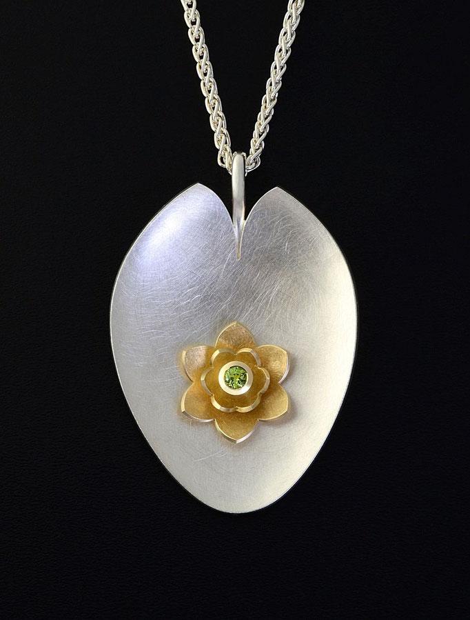 schmuckdesign Seerose in Gelbgold mit Peridot, auf einem handgeschmiedeten silbernen Seerosenblatt.