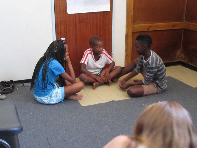 Das Theaterstück, die Kinder spielen Karten im Schulhof