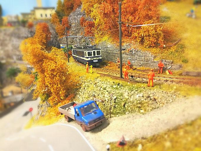 An der Gleisbaustelle machen die Arbeiter Platz für einen bergwärts fahrenden Regionalzug.