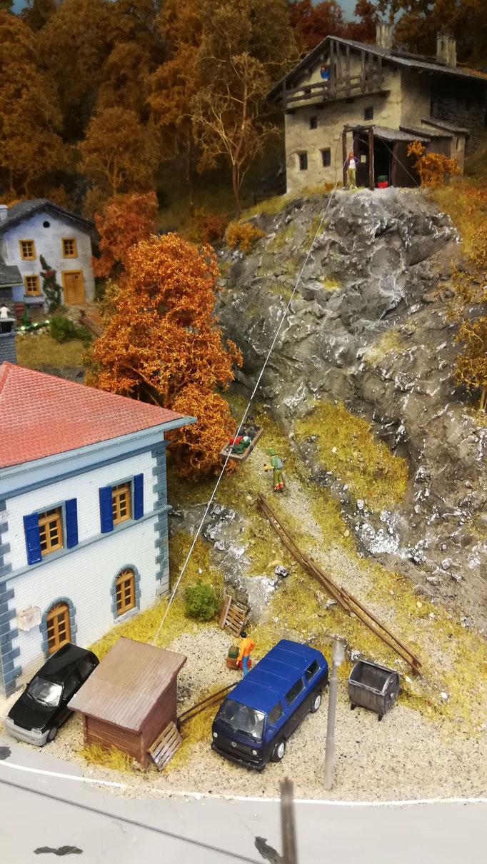 Zwischen den Häusern führt auch ein beliebter Wanderweg in die Berge. Hier ist auch die Materialseilbahn zu sehen, die das oberste Gebäude versorgt.