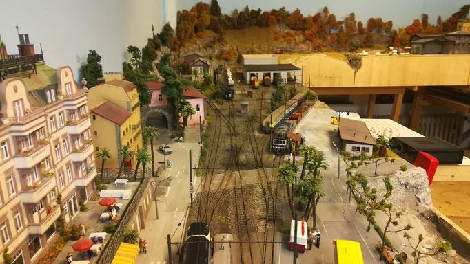Übersichtsbild über die Depot- und Abstellanlage, das von links einmündende Streckengleis und den in Bahnhofsmitte befindlichen Bahnübergang.