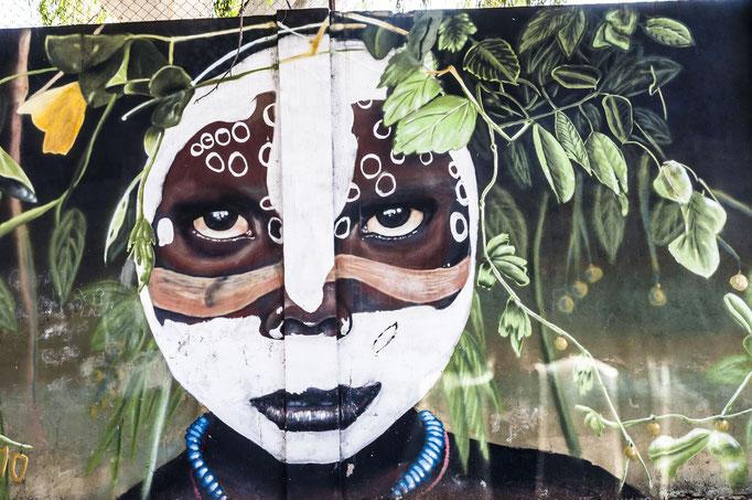 Der Künstler Primo malte diese pflanzenbedeckte, afrikanische Stammesangehörige.