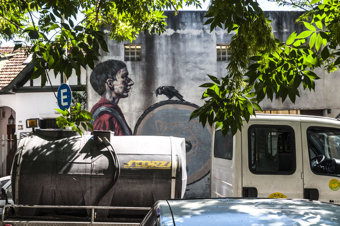 Das Mural aus 2016 von Milu Correch zeigt zwei sich gegenüberstehende Trommler. Hier zu sehen der linke Trommler mit einer Krähe auf der Trommel.