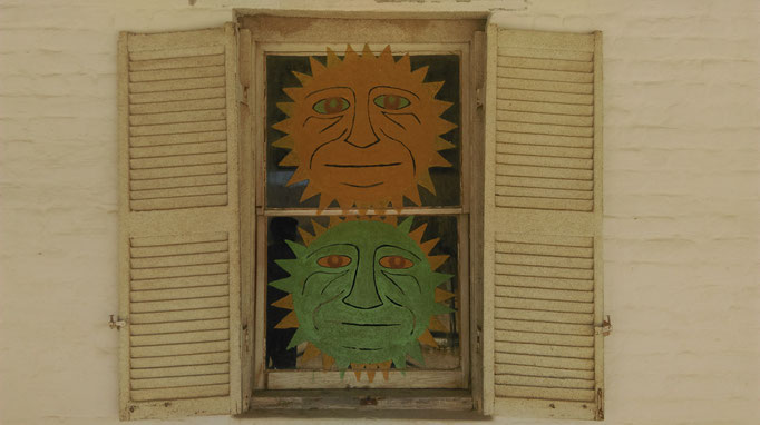 The two suns on the window at the front of the Owl House, Nieu-Bethesda, South Africa.