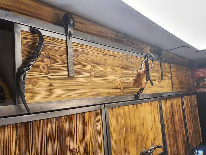 Schiebetür über den Hängeschränken mit geschmiedetem Türgriff