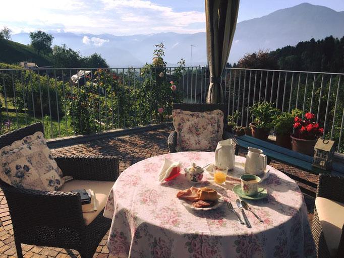 Colazione all'aperto al B&B Monti del Sole a Pedavena, profumo di fiori, rose, e intenso gelsomino, panorama sull'antica cittadina murata di Feltre