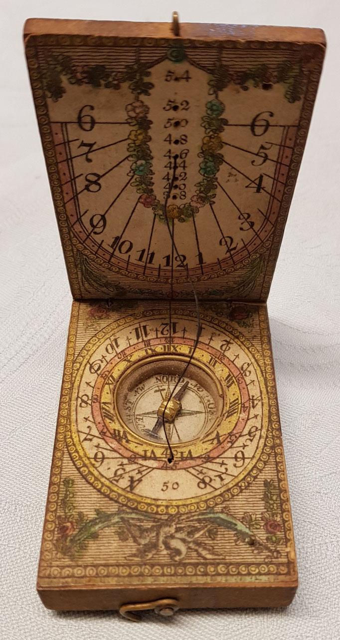 Inv.-Nr. Td 0089. Taschensonnenuhr mit eingebautem Kompass. Verm. Ende 18. Jh (oder spätere Kopie). Holz und Papier. Hersteller: verm. Beringer, Nürnberg. 4.5x7 cm