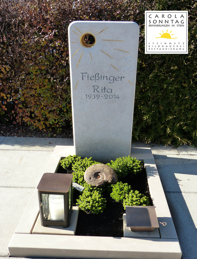 Urnengrab in hellem Kalkstein mit Sonnenmotiv und vergoldeten Strahlen